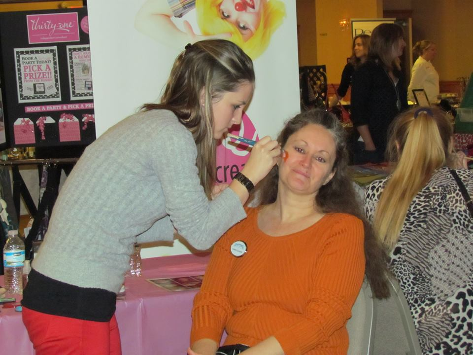 Karen Coleman, Director, gets her face painted by Bre Creative.