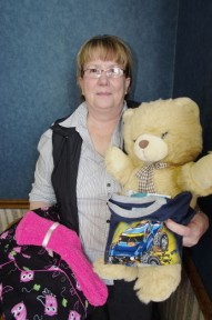 Karen Geerts with stuffed toys and pyjamas to be packaged and given to a family in need.